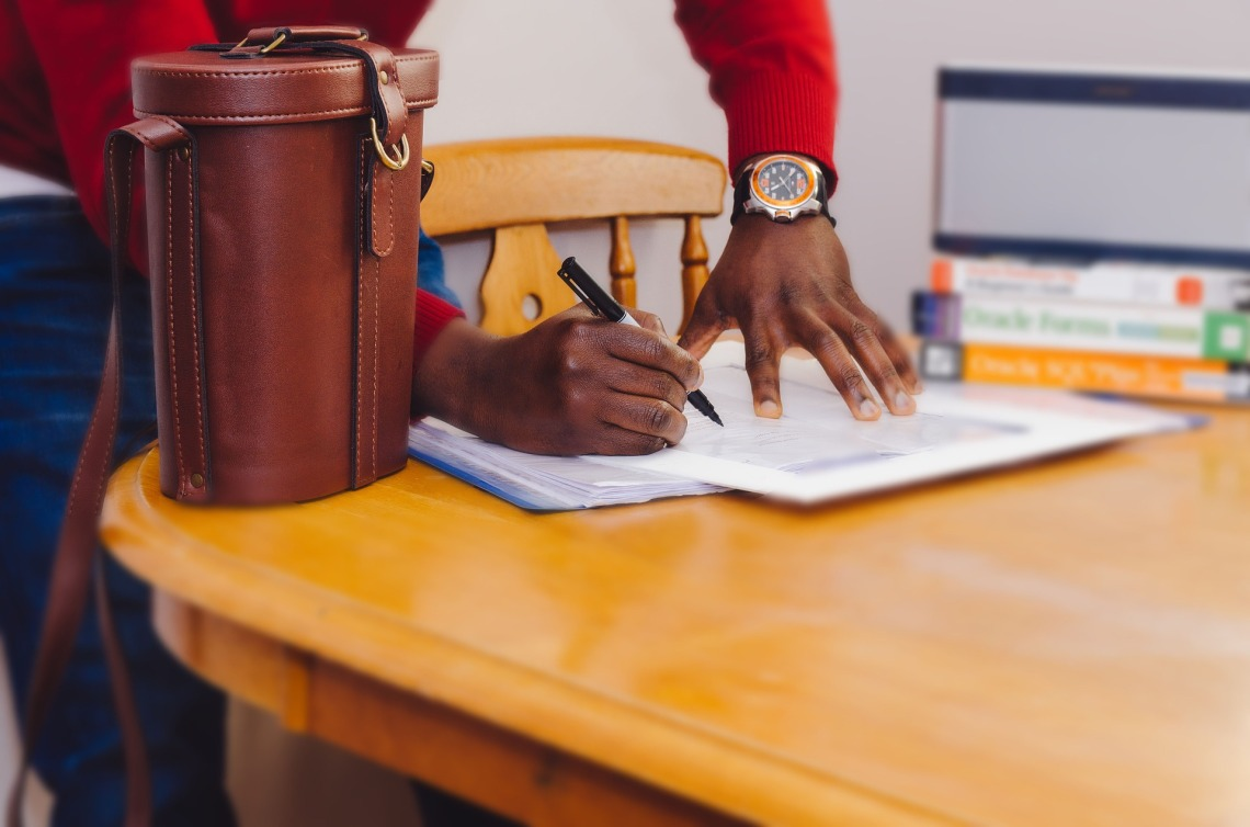 Paper on a dining table, between a stack of books and a satchel. A person in a red jumper and a big watch stands behind the chair and writes with a marker pen