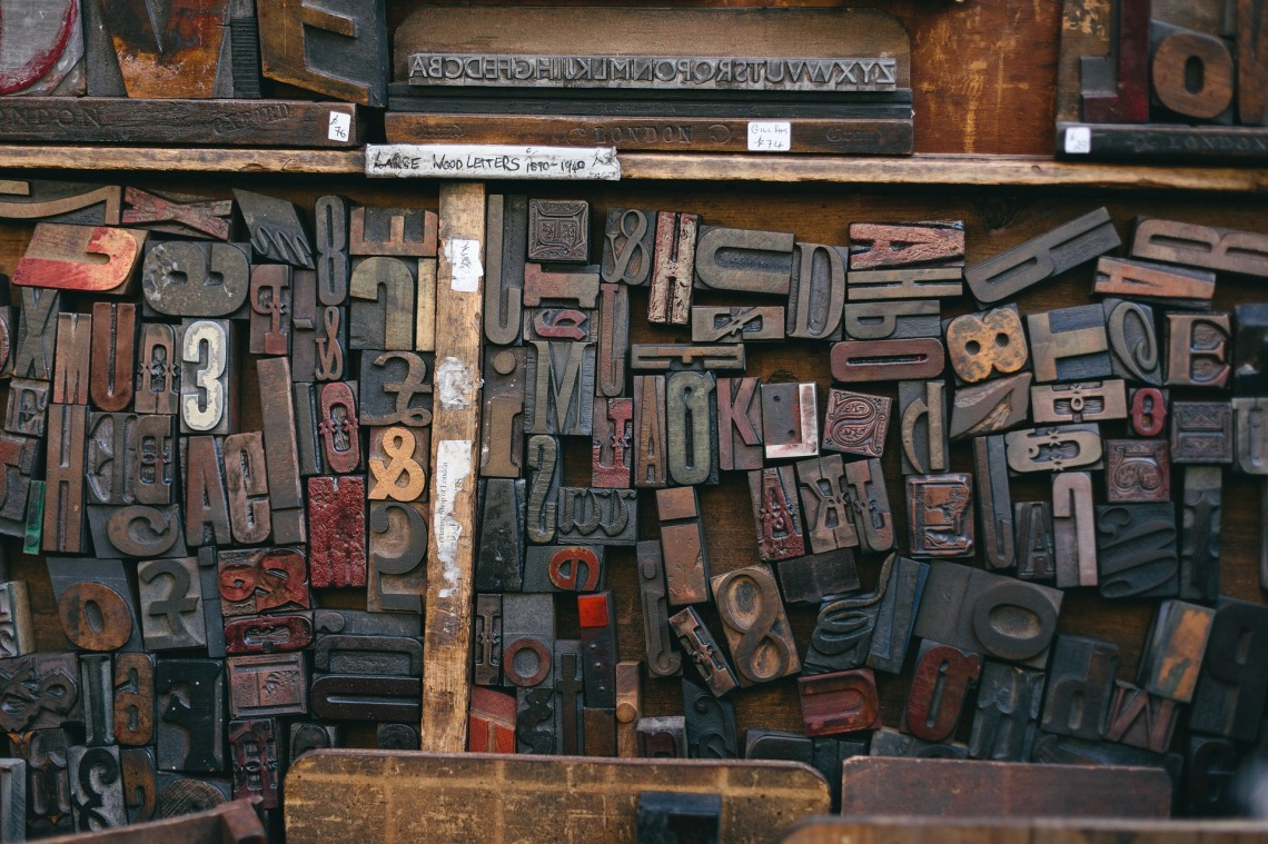 A jumble of vintage wooden and metal printers type blocks