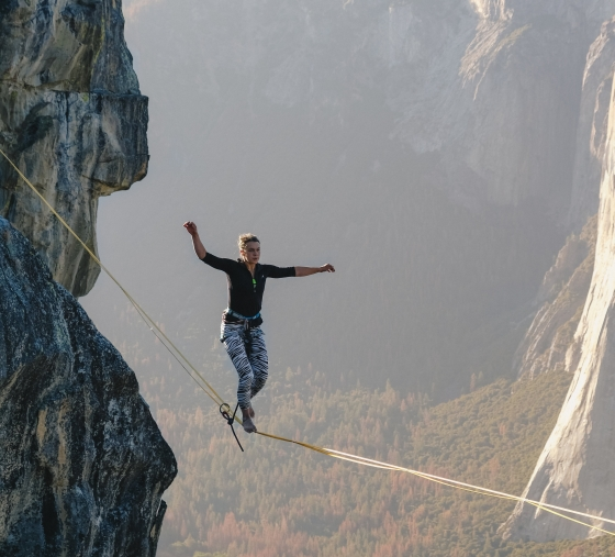 Woman on a tightrope above a valley with sheer rock side to the left and far away to the right